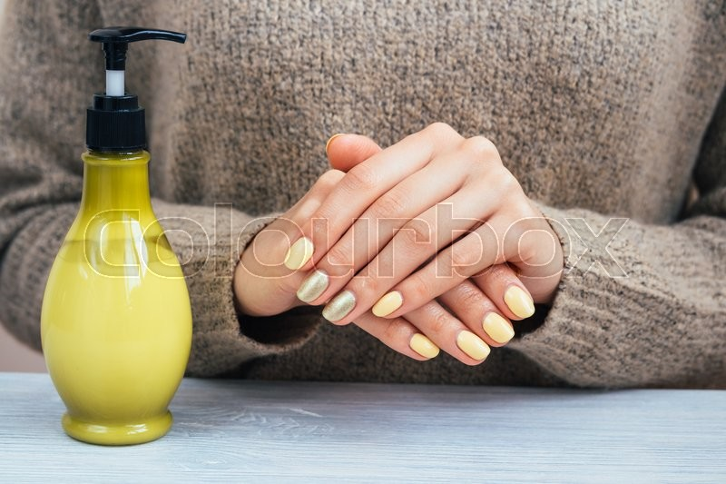 Stock image of 'Woman in a brown sweater showing hands with yellow manicure, close-up'