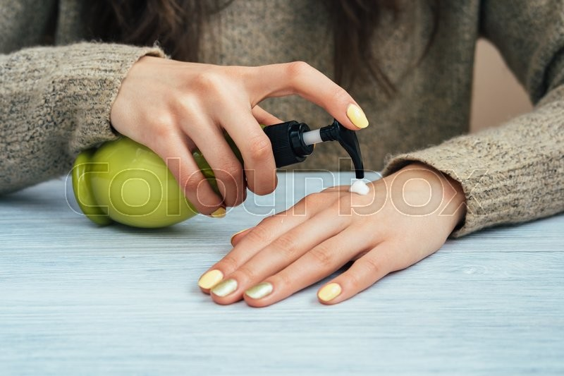 Stock image of 'Girl in brown sweater with yellow manicure applying hand cream, close-up'