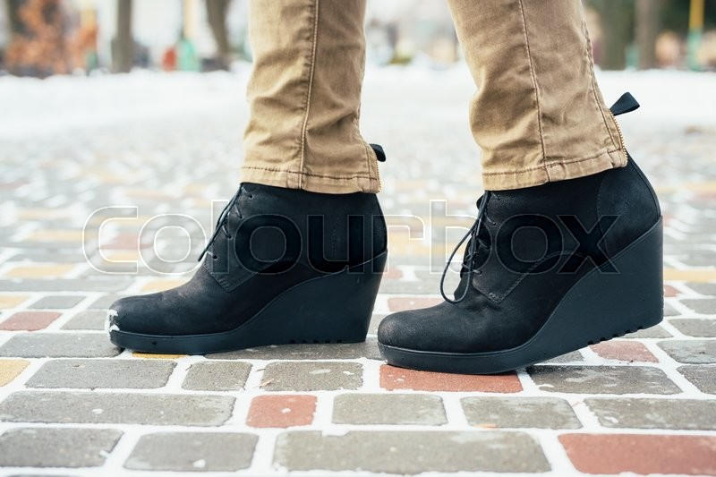 Stock image of 'Female feet in black boots standing on the sidewalk in the winter, close-up'