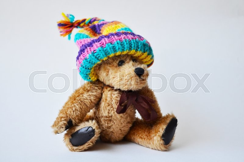 Stock image of 'Toy teddy-bear wearing a striped bobble cap'