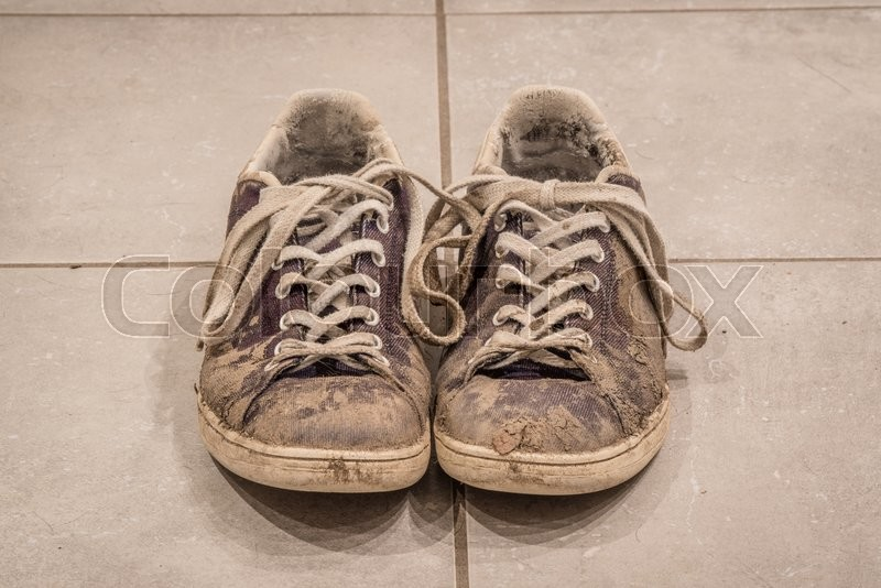 Stock image of 'Pair of dirty shoes with mud on the floor'