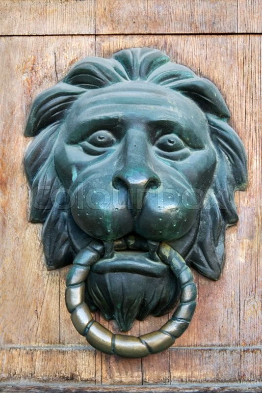 Stock image of 'Door handle in the form of a lion's head on the gate'