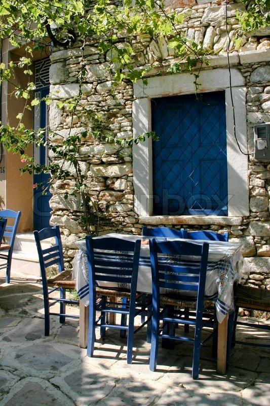 Traditionel græsk udendørs værtshus bord og blå stole  stock foto ...