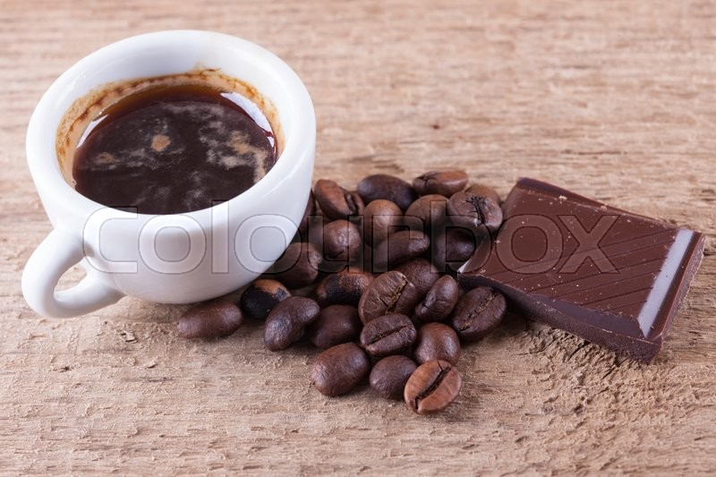 Stock image of 'Cup, coffee beans, chocolate, wooden board closeup top view background'