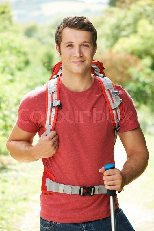 Stock image of 'Young Man Hiking Through Countryside'