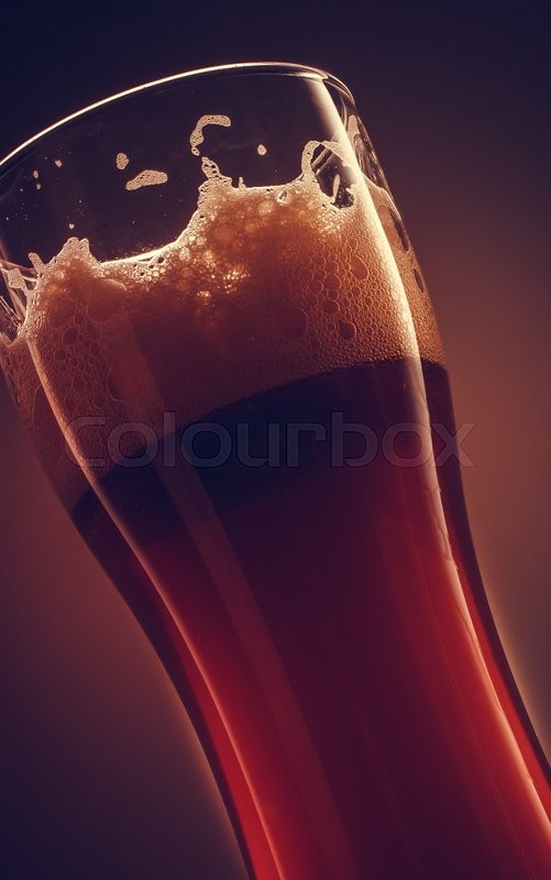 Stock image of 'Glass of beer with foam on top in close up with color background'