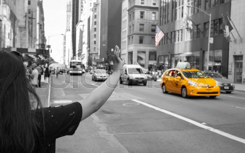 Stock image of 'Tourist call a yellow cab in Manhattan with typical gesture with arm up. The taxicabs of New York City are widely recognized icons of the city.'