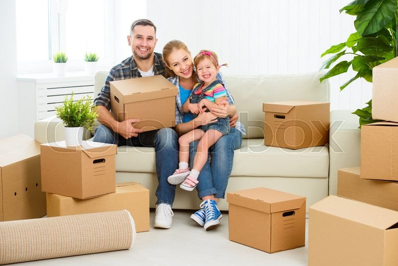Stock image of 'moving to a new home. Happy family with cardboard boxes'