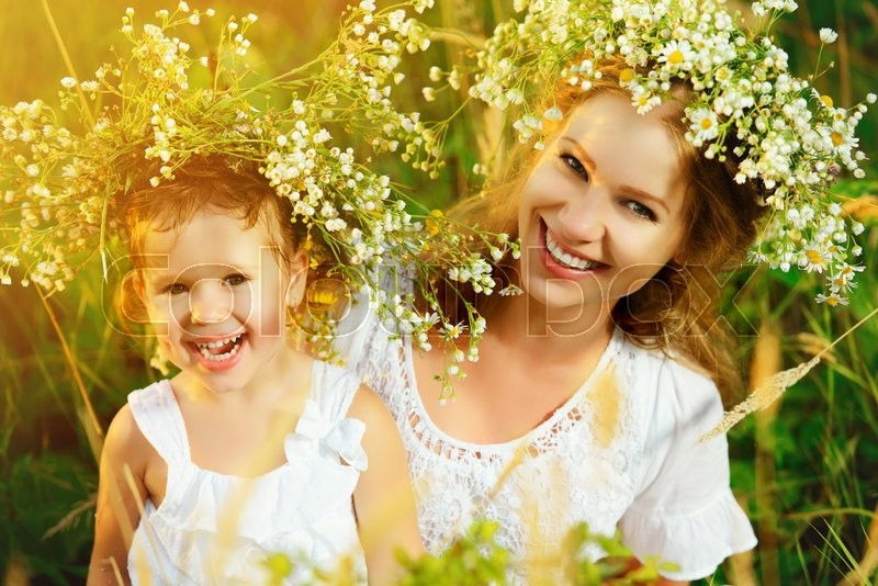 Stock image of 'happy laughing family, daughter hugging mother in wreaths of summer flowers in nature'