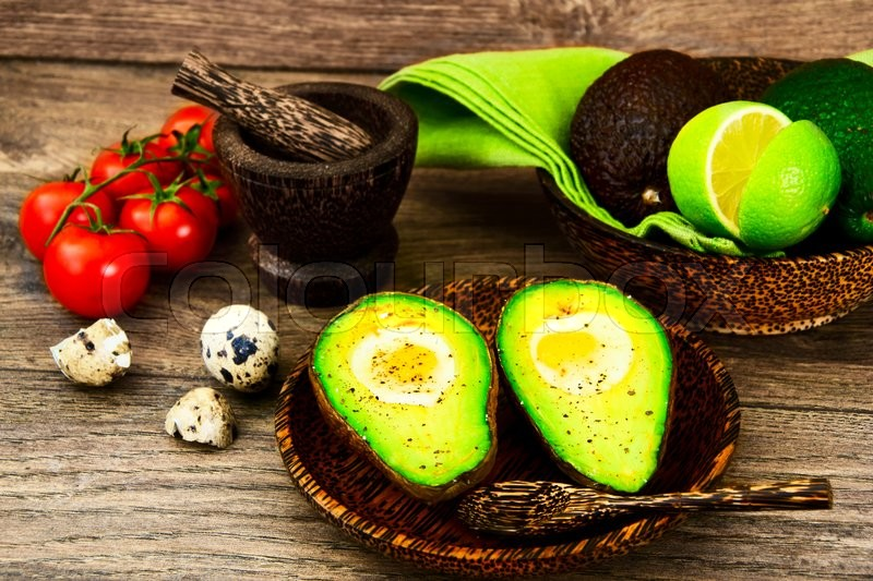 Stock image of 'Avocados, Baked with Quail Egg, Salt, Pepper and Lemon Studio Photo'