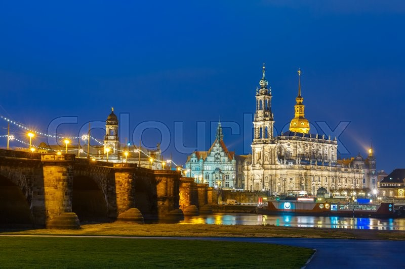 Stock image of 'Dresden Cathedral of the Holy Trinity aka Hofkirche Kathedrale Sanctissima Trinitatis and Augustus Bridge with reflections in the river Elbe at night in Dresden, Saxony, Germany'