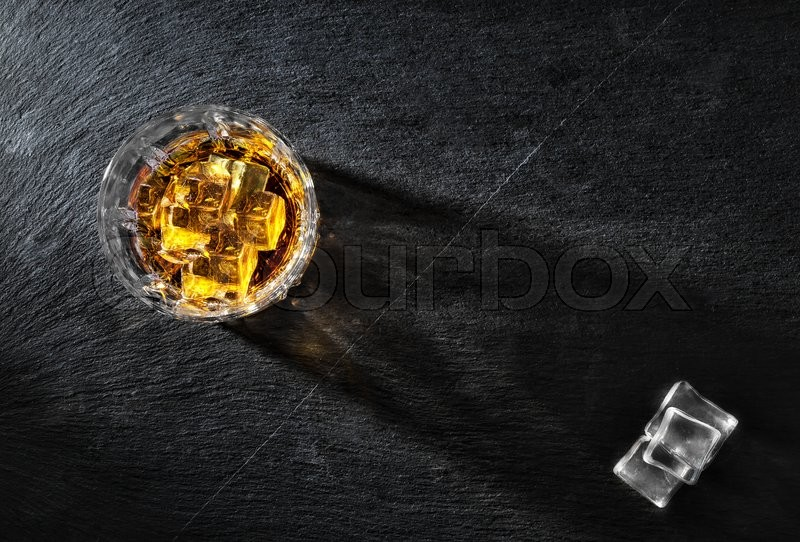 Stock image of 'Glass of whiskey with ice on black textural background shot from above'