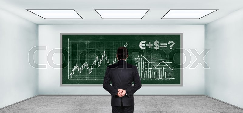 Stock image of 'businessman looking on drawing stock chart on blackboard in empty room'