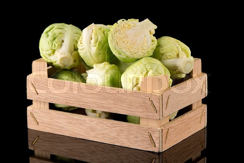 Stock image of 'Fresh brussels sprouts on wooden box isolated on black background.'