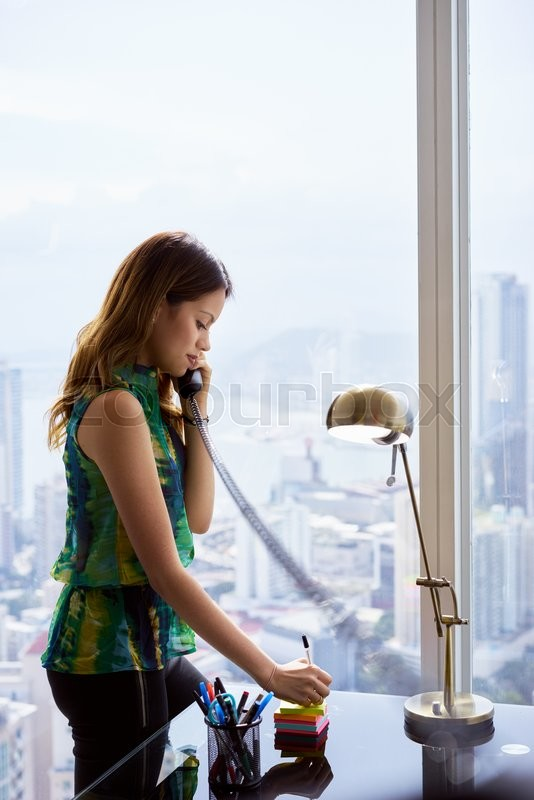 Stock image of 'Young hispanic businesswoman in a modern office building, with a beautiful sight of the city in background. She holds a wired telephone and writes a message on adhesive note. Copy space'