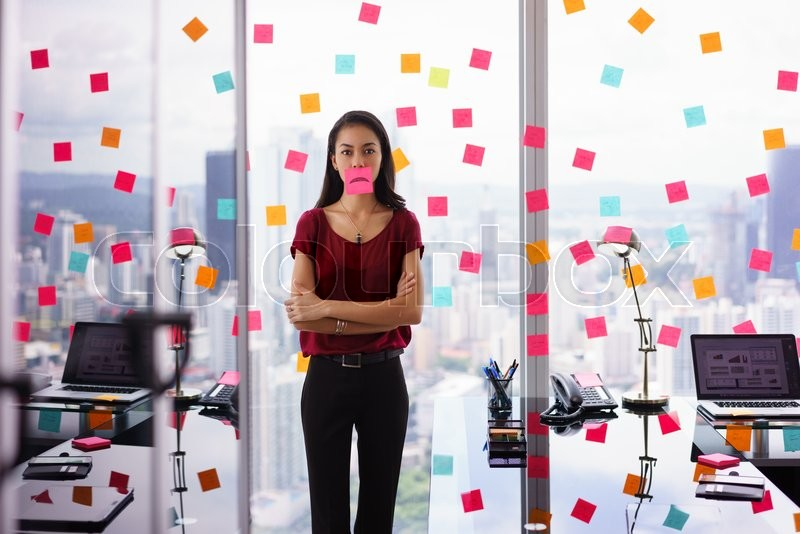 Stock image of 'Mixed race woman working in modern office with reminders on skyscraper window. The girl feels stressed, holds a sticking note with sad emoticon on mouth.'