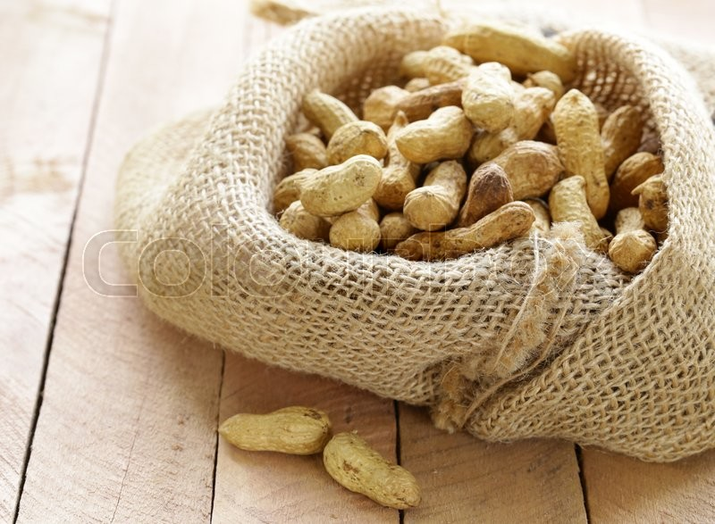 Stock image of 'peanuts nuts in a bag on wooden table'