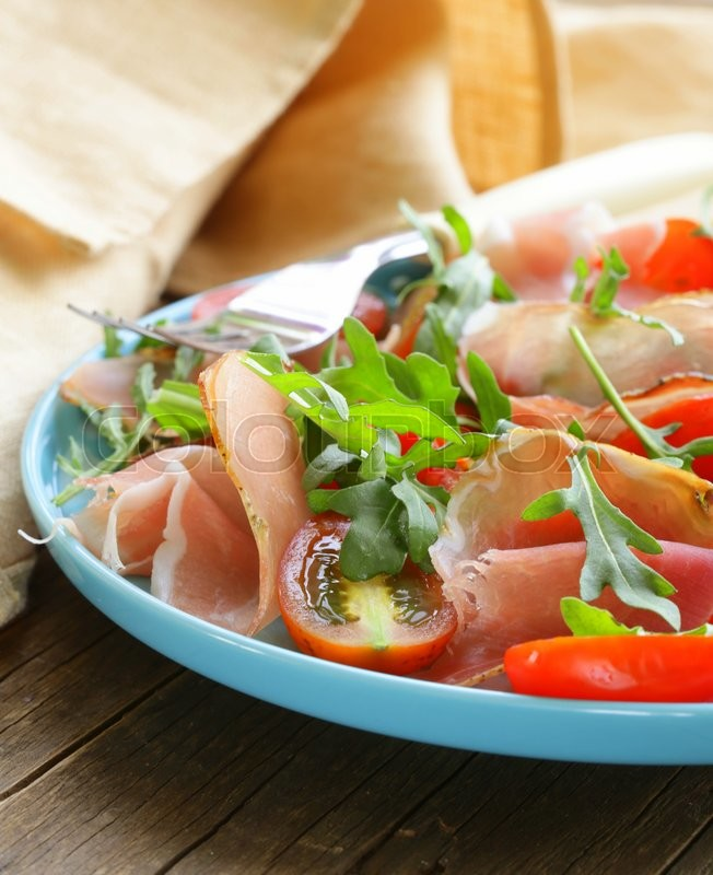 Stock image of 'salad with parma ham (jamon), tomatoes and arugula'