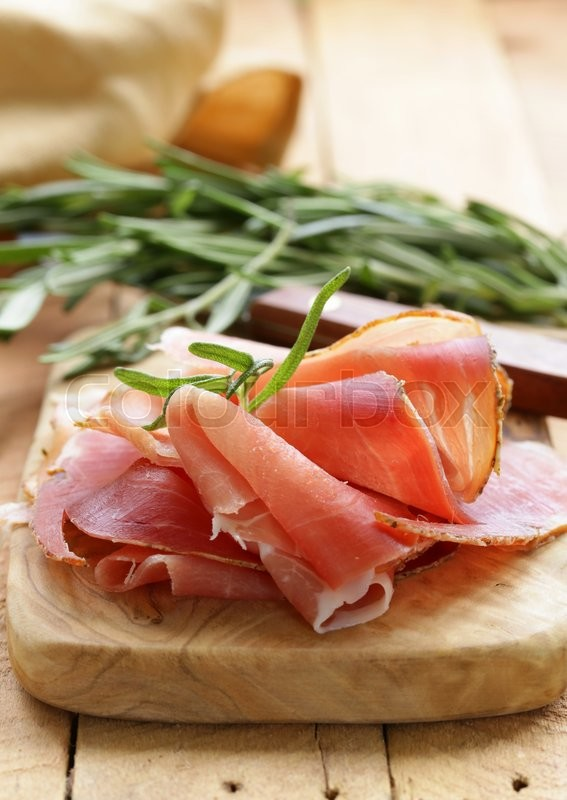 Stock image of 'parma ham (jamon) sliced on a wooden board'