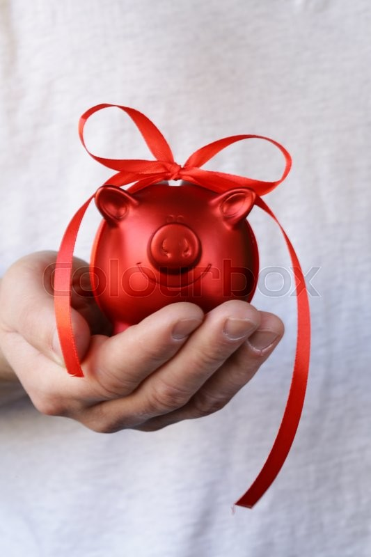 Stock image of 'Red piggy bank with gift ribbon'
