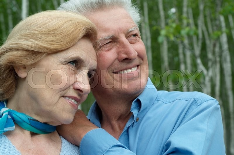 Stock image of 'Loving mature couple sitting in summer park'