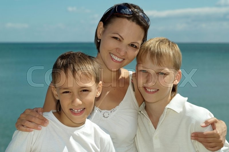 Stock image of 'Mother and children on the background of the sea'