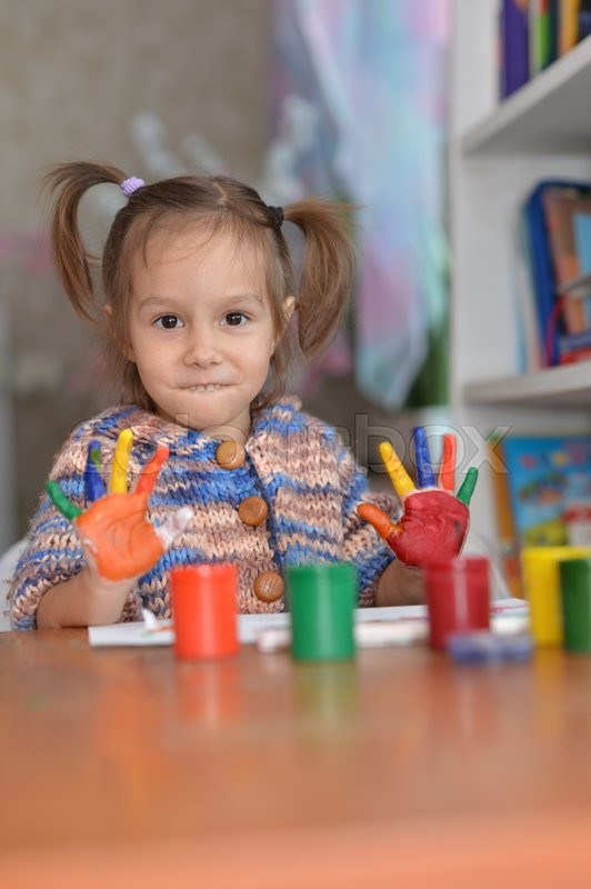 Stock image of 'Little girl drawing with paints at home'