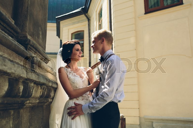 Stock image of 'The bride and groom posing in the old street'