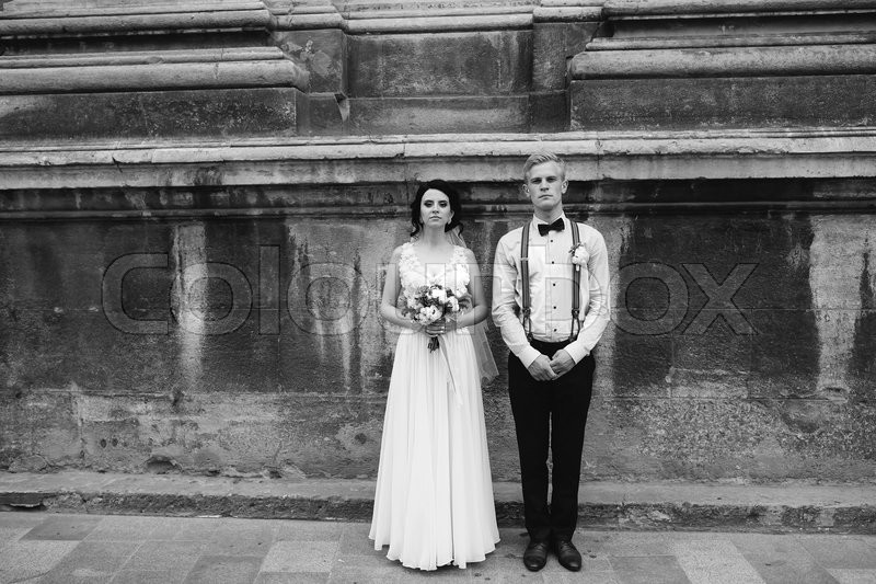 Stock image of 'The bride and groom posing in the old street, family photo'