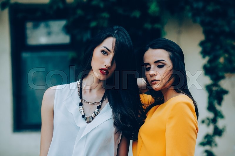 Stock image of 'Two beautiful young girls in dresses posing in front of house'