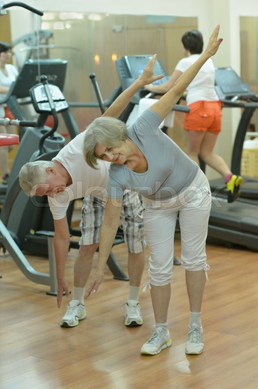 Stock image of 'Active smiling senior couple exercising in gym'