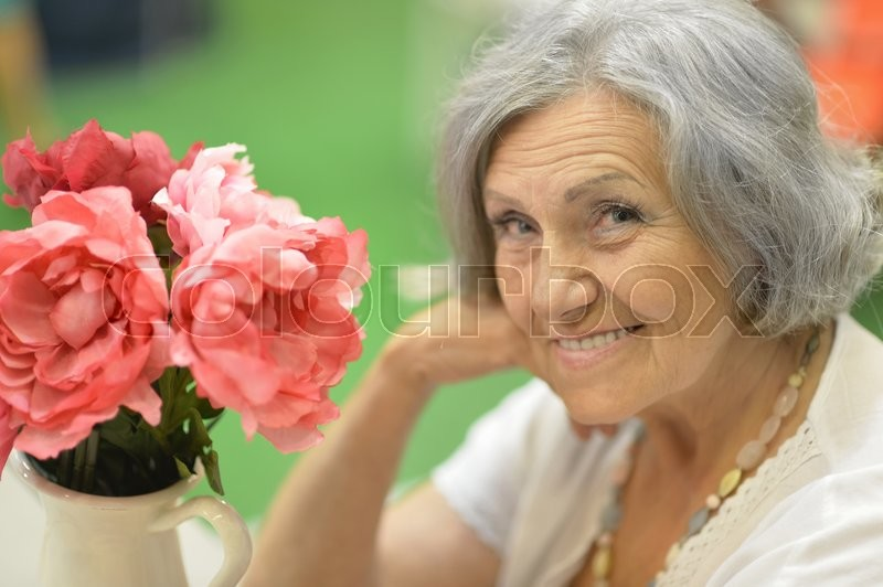 Stock image of 'Portrait of beautiful senior woman with flowers in vase'