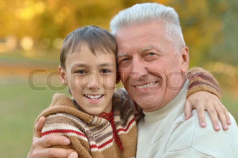 Stock image of 'Grandfather and grandson together in autumn park'