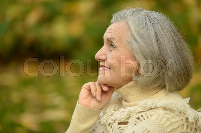 Stock image of 'Happy beautiful senior woman in the autumn park'