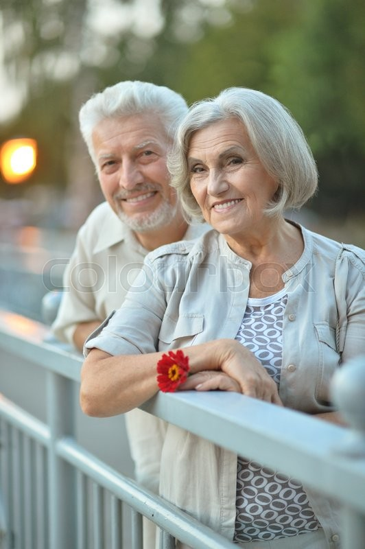 Stock image of 'Amusing happy smiling old couple with flower'