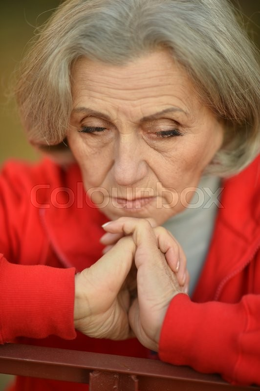 Stock image of 'Nice sad old woman on the autumn background'