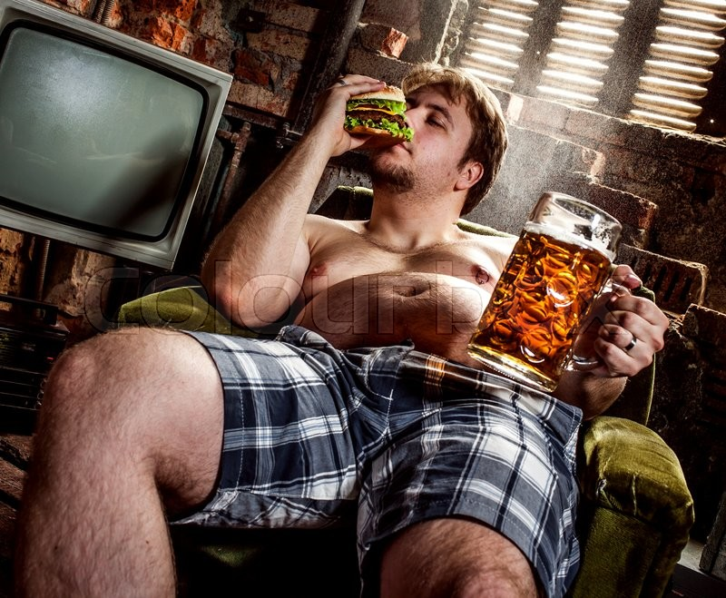 Stock image of 'fat man eating hamburger seated on armchair'