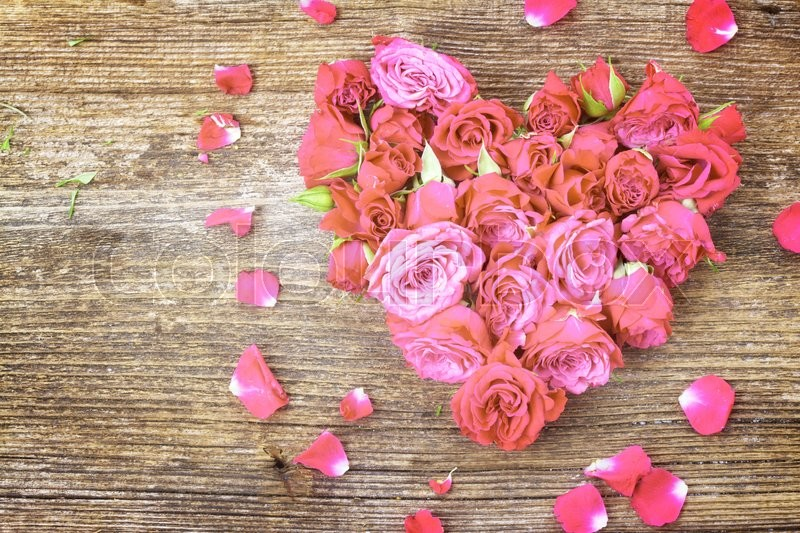 Stock image of 'pile  of  mauve small fresh  roses in heart shape  and petals   on wooden table background, retro toned'