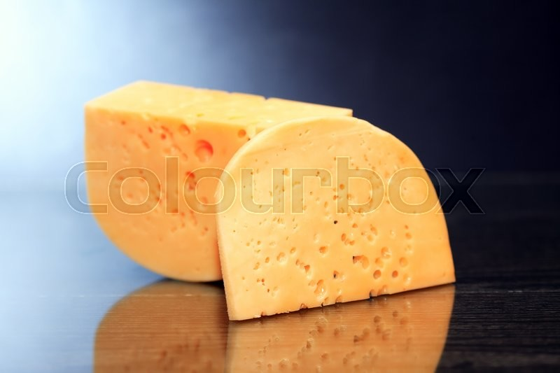 Stock image of 'Piece of cheese on nice dark background with reverberation'