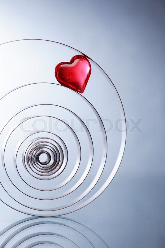 Stock image of 'Love or medical concept. Red glass heart inside metal spiral on nice gray background'