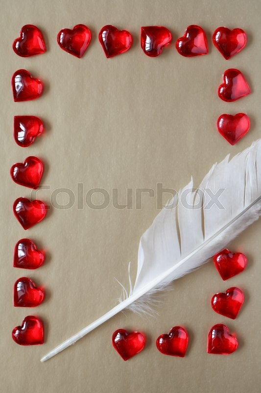 Stock image of 'Love concept. Quill pen and red hearts as frame on paper background'