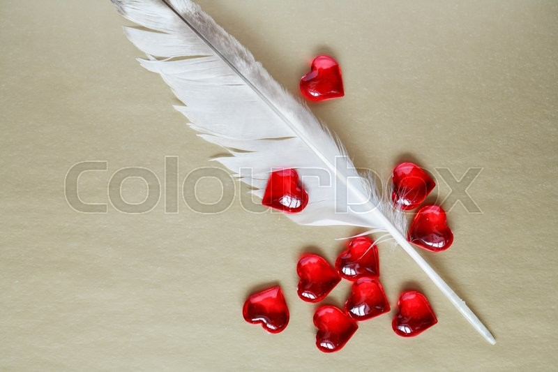 Stock image of 'Love concept. Quill pen and red hearts on paper background'