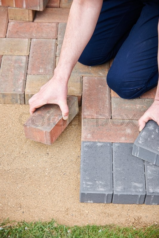 Stock image of 'Man Laying Blocks For Patio'