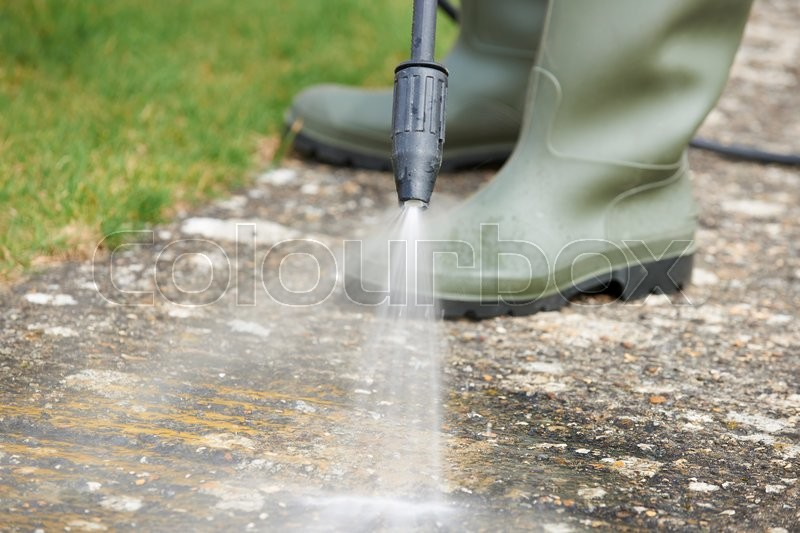 Stock image of 'Man Washing Concrete Path With Pressure Washer'