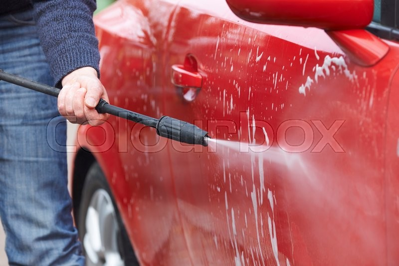 Stock image of 'Man Washing Car With Pressure Washer'