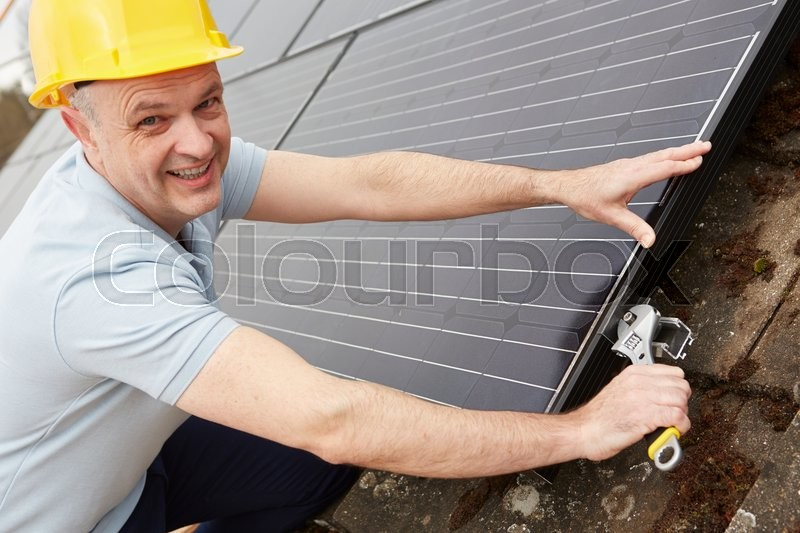 Stock image of 'Engineer Installing Solar Panels On Roof Of House'