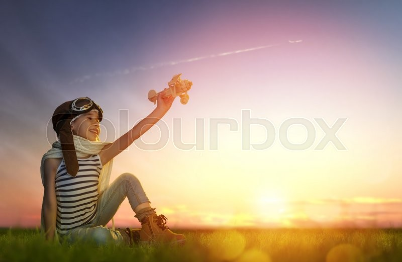 Stock image of 'dreams of flight! child playing with toy airplane against the sky at sunset'