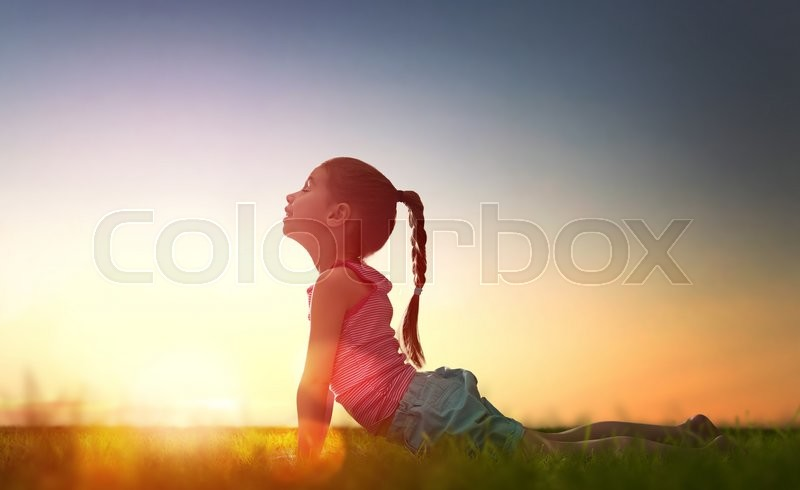 Stock image of 'Child girl in the Park. Yoga at sunset in the park. Girl is practicing yoga.'