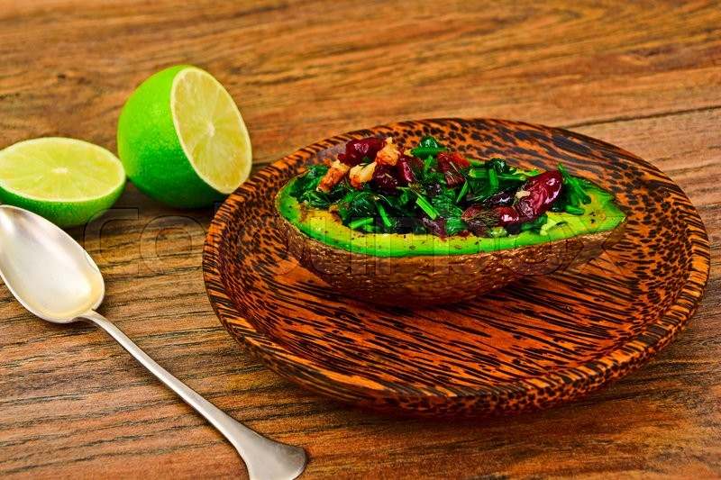 Stock image of 'Avocado salad with herbs dill, parsley, cilantro, nuts and sun-dried cranberries Studio Photo'