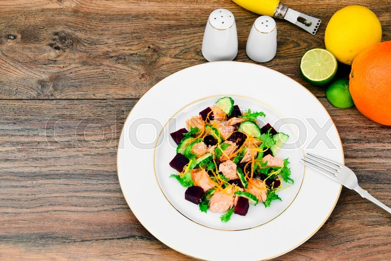 Stock image of 'Salad with Beets, Salmon, Cucumber, Arugula, Lemon Zest, Orange, Olive Oil and Pepper Studio Photo'